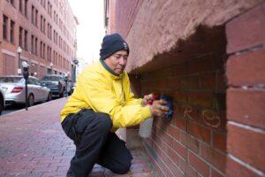 Pedro removing graffiti